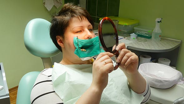 Thumbnail for Woman Looking At Mirror In The Dentists Chair