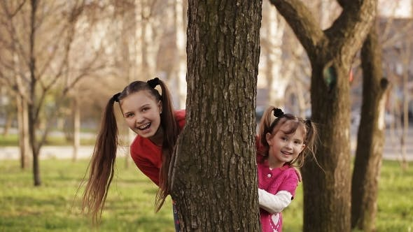 Cover Image for Cheerful Girl Playing Hide And Seek Behind a Tree