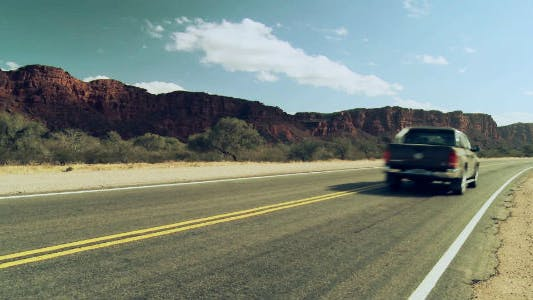 Thumbnail for Pickup Truck driving fast on a Long Straight Desert Road.