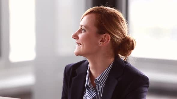Thumbnail for Young Businesswoman Listening And Nodding During Corporate Presentation