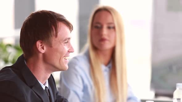 Thumbnail for Businessman Talking In Meeting, Female Colleague In Background