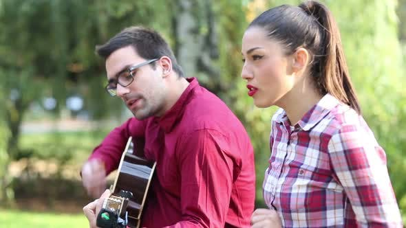 Thumbnail for Young Couple Playing Guitar And Singing In Park 3