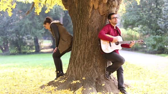 Thumbnail for Young Couple Playing Guitar And Singing While Leaning Against Tree In Park