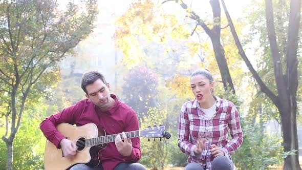 Thumbnail for Young Man And Women Playing Guitar And Singing In Park 5