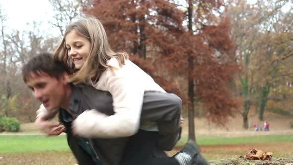 Thumbnail for Mädchen springt auf Papas zurück in die Park