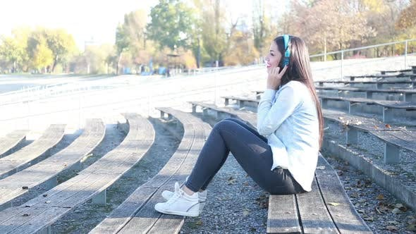 Thumbnail for Attractive Brunette Woman Listening To Music With Headphones At Park 2