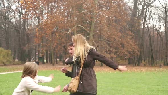 Thumbnail for Girl Playing With Her Parents In Park