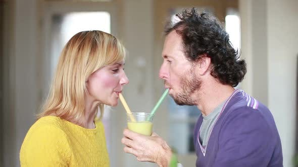 Couple Drinking Smoothie From Same Drinking Glass