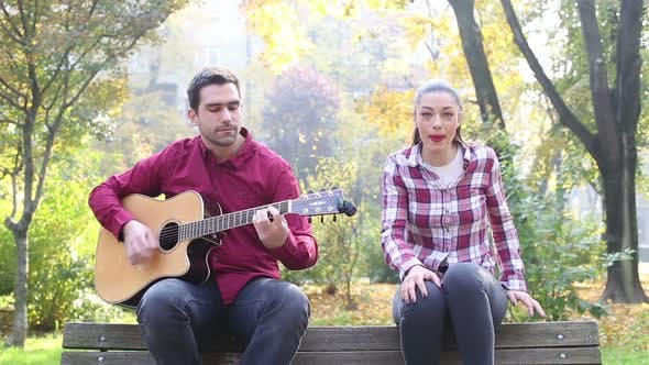 Thumbnail for Beautiful Brunette Woman Singing And Man Playing Guitar In Park 2