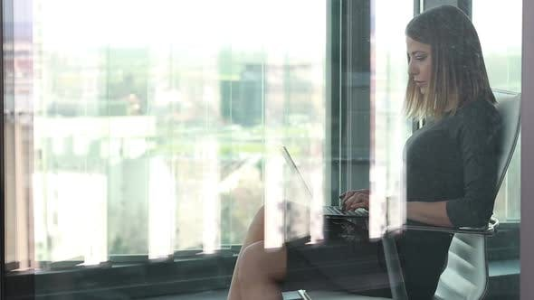 Thumbnail for Beautiful Businesswoman Sitting On Chair With Laptop Behind Glass Wall