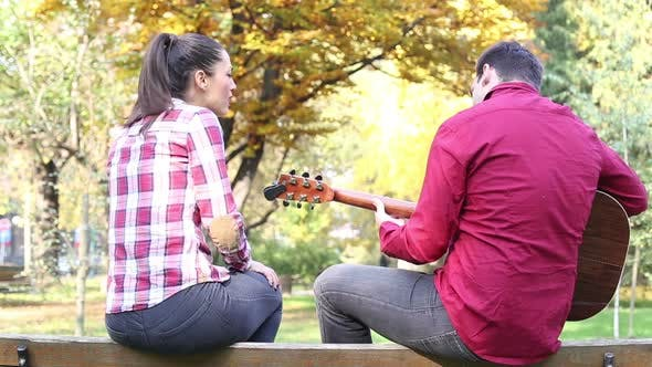 Thumbnail for Couple Sitting On Park Bench, Man Playing Guitar While Woman Singing 4