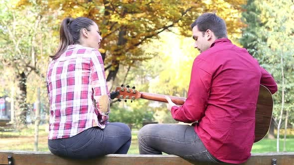 Thumbnail for Couple Sitting On Park Bench, Man Playing Guitar While Woman Singing 5