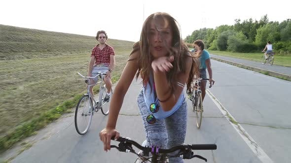Thumbnail for Beautiful Woman Sending Kisses While Cycling With Friends 3