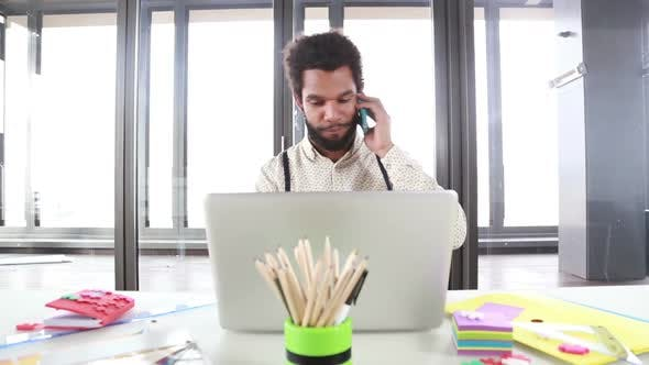 Thumbnail for Male Creative Executive Talking On Phone While Working On Laptop