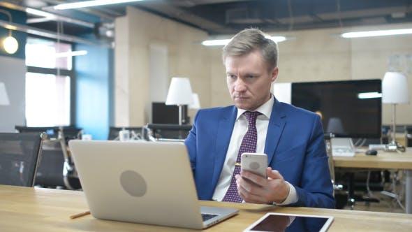 Thumbnail for Geschäftsmann arbeitet mit Laptop und Smartphone