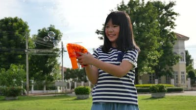 Beautiful Girl Shooting Bubbles From Bubble Gun In The Park