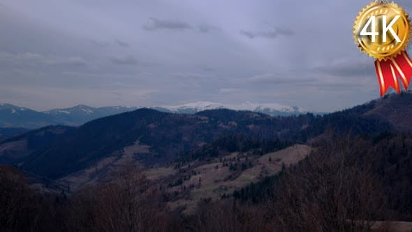 Thumbnail for Clouds Moving Across a Snowy Mountains Landscape