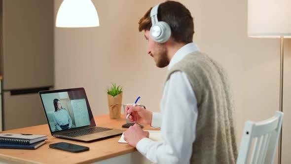 Der Student des jungen Mannes sitzt zu Hause an einem Schreibtisch und lernt online mit einem Laptop, der in einer Fernbedienung lernt
