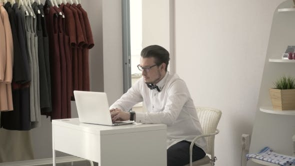 Thumbnail for Young Fashion Designer Typing On Laptop At Workplace