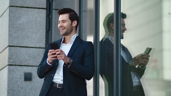 Cover Image for Closeup Man Standing in Black Suit at Street. Businessman Using Smartphone