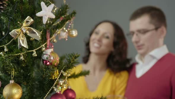 Loving Couple Admiring Merry Twinkling of Festive Lights Standing in Embrace