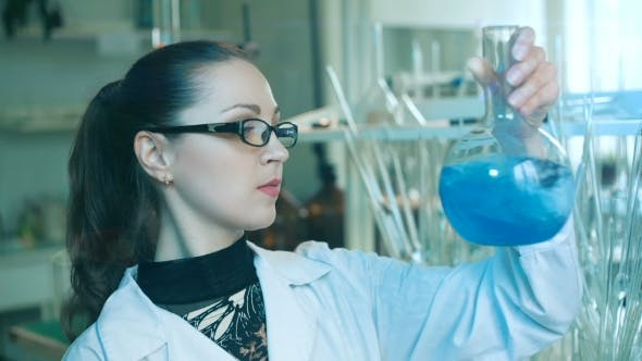 Thumbnail for Woman Shakes Flask In a Laboratory