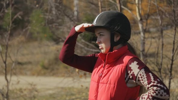 Thumbnail for Woman Jockey Standing And Looking Into Distance Keeping Hand As a Visor