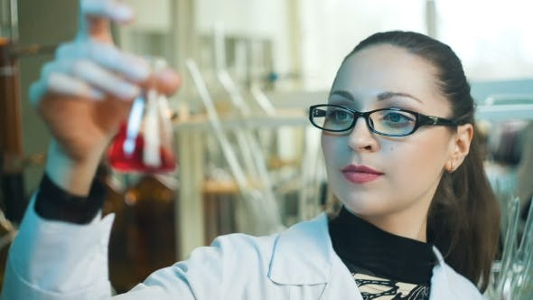 Woman Working Look At Flasks In a Laboratory