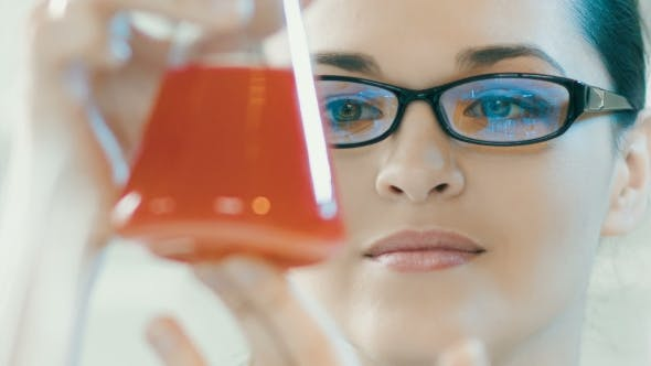 Woman Look At Flask In a Laboratory