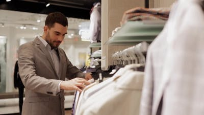Young Man Choosing Clothes In Clothing Store 23