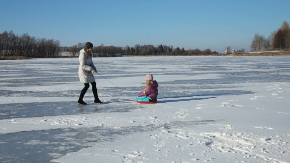 Thumbnail for Mother And Daughter Sledding On Frozen Lake