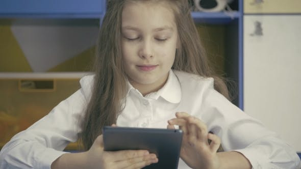 Thumbnail for Cute Little Girl Studying At The Library Doing Homework With Tablet PC