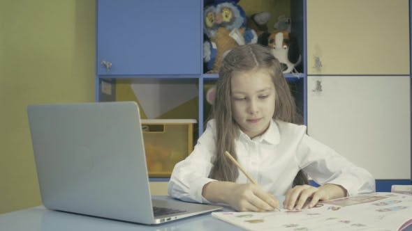 Thumbnail for Young Girl Using a Laptop And Doing Homework In School