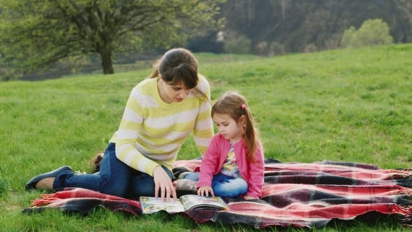 Thumbnail for Attractive Young Woman Reads a Book a Little Girl
