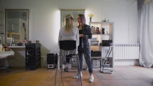 The Friendly Stylist Working With His Regular Customer In a Beauty Salon