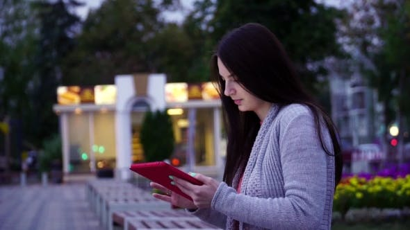 Thumbnail for Girl Sitting On a Bench In The Park And Use Applications In The Computer Tablet