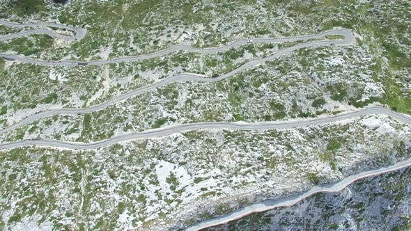 Aerial view of asphalt road curving on a hill