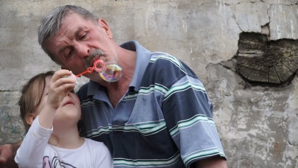 Thumbnail for Grandfather With His Granddaughter Blow Bubbles