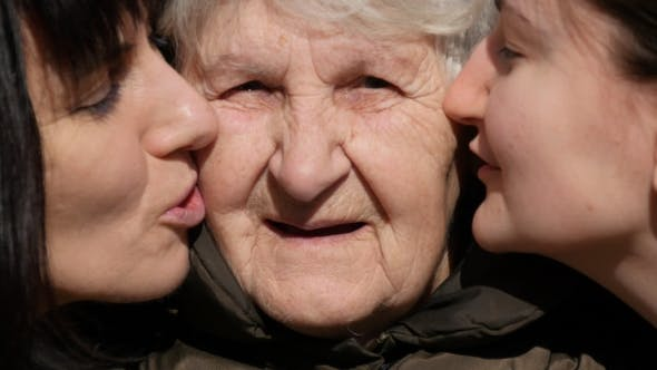 Thumbnail for Young Girl And Adult Woman Kissing Grandmother On Cheeks