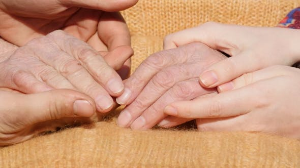Thumbnail for A Young Man's And Woman's Hands Comforting a Old Pair Of Hands Of Grandmother Outdoor