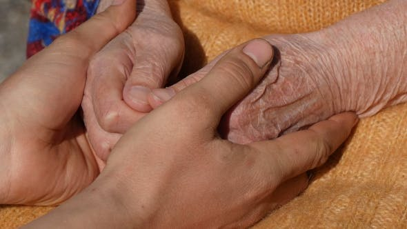 Thumbnail for A Young Dirty Working Male Hands Comforting An Elderly Pair Of Hands Of Grandmother Outdoor .