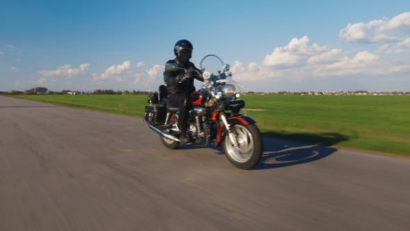 Thumbnail for Biker Rides On The Road On a Background Of Green Fields