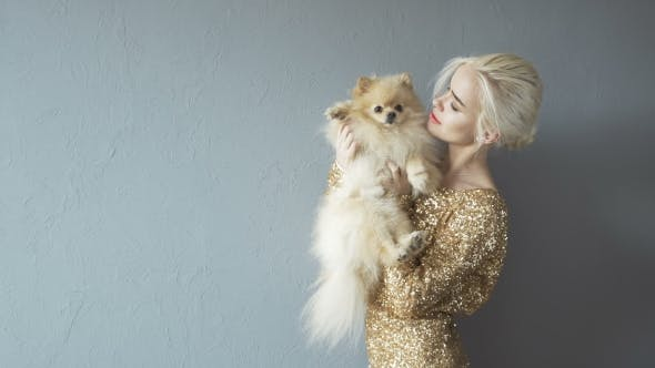 Thumbnail for Beautiful Blonde Woman With Her Spitz Isolated On Grey