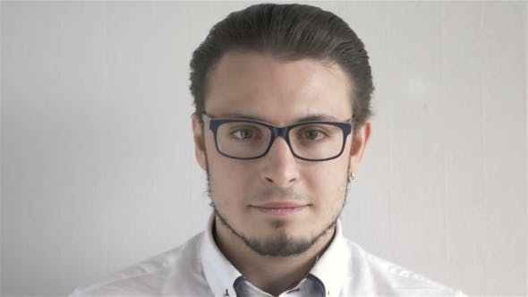 Thumbnail for Portrait Of Attractive Young Man With Glasses Standing On Gray Background