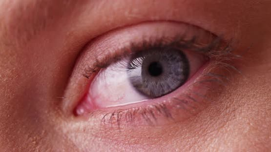 Extreme close up of young woman's blue eye front view dramatic lighting