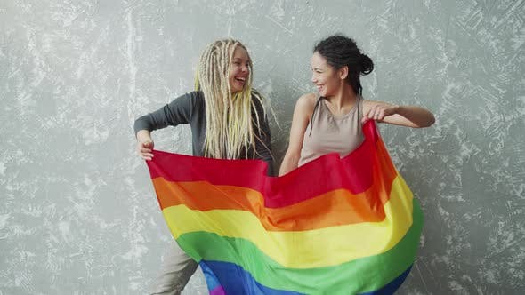 Positive Girlfriends Waving a LGBTQ Flag and Looking Into Each Other Eyes