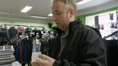Man Shopping For Clothes And Speaks To Cashier