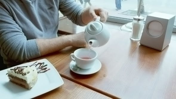 Man Pours Tea From Teapot Spills And Wipes Table