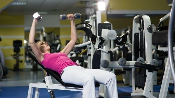 Fit Attraktive Frau liegend auf Trainingsgerät