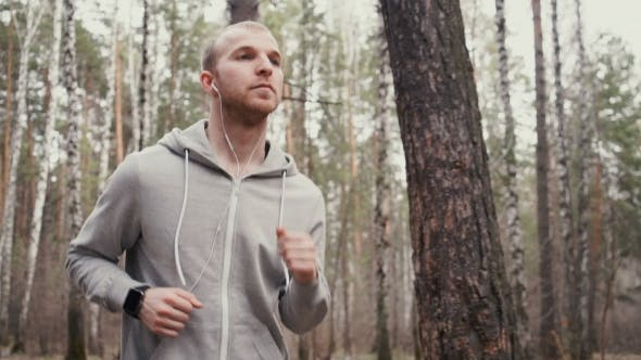 Man Running In Forest Woods Training And Look At Smart Watches